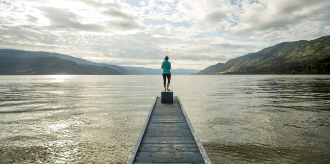 Woman stand at end of pier above lake